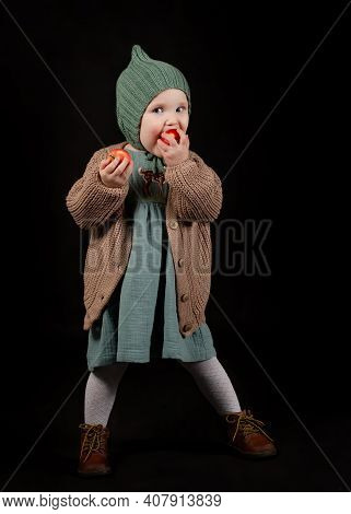 Portrait Of Little Girl (toddler), Dressed In Cozy Vintage Clothes. She Poses And Nibbles An Apple.