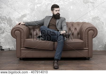 Elegant And Confident. Man Of Fashion. Fashion Model Relaxing On Sofa. Bearded Man Enjoying Casual F