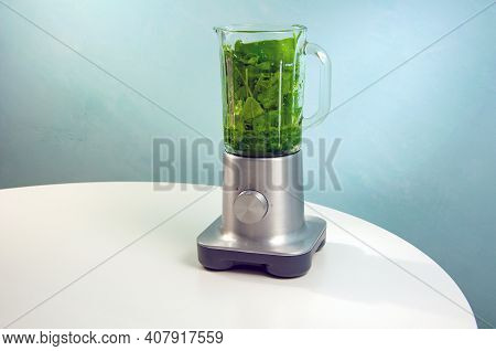 A Blender With A Glass Jug Stands On A White Table.