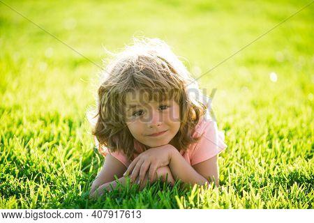 Child In Park Outdoor. Spring Kid Lying On Grass. Summer Boy Walk. Children Adaptation