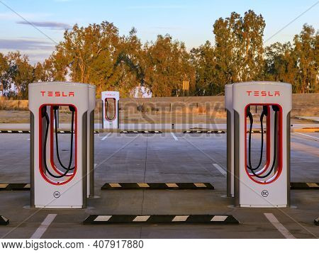 Firebaugh, Usa - January 21, 2021: Rows Of Empty Electric Tesla Superchargers By California Highway
