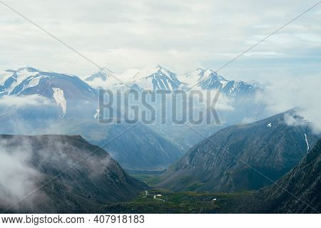 Beautiful Atmospheric Alpine Landscape To Big Snowy Mountains With Glacier. Low Clouds Among Rocks I