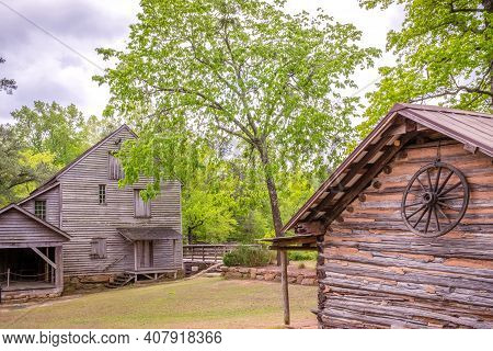 The Old Gristmill Structure And An Ash Tree At Historic Yates Mill County Park In Raleigh, North Car