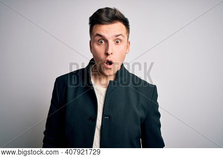 Young handsome business mas wearing elegant winter coat standing over isolated background afraid and shocked with surprise expression, fear and excited face.
