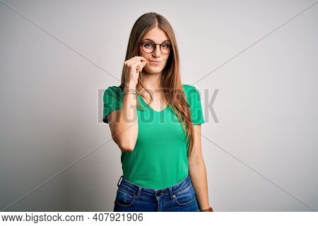 Young beautiful redhead woman wearing casual green t-shirt and glasses over white background mouth and lips shut as zip with fingers. Secret and silent, taboo talking