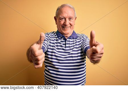 Grey haired senior man wearing casual navy striped t-shirt standing over yellow background approving doing positive gesture with hand, thumbs up smiling and happy for success. Winner gesture.