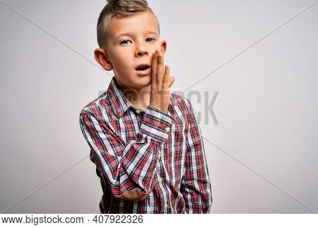 Young little caucasian kid with blue eyes wearing elegant shirt standing over isolated background hand on mouth telling secret rumor, whispering malicious talk conversation