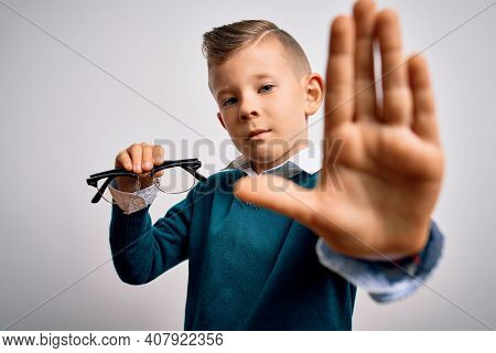 Young little caucasian kid holding eyesight glasses correction over isolated background with open hand doing stop sign with serious and confident expression, defense gesture
