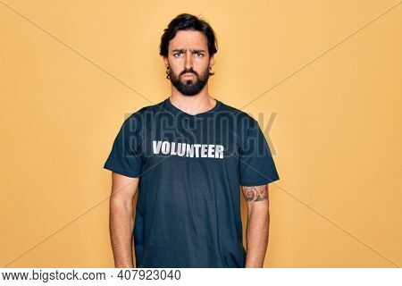 Young handsome hispanic volunteer man wearing volunteering t-shirt as social care depressed and worry for distress, crying angry and afraid. Sad expression.