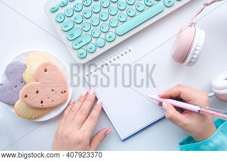 Female Hands In A Blue Blouse Write With A Pen In A Notebook, A Plate With Heart Cookies, A Blue Key