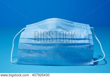 Prevent coronavirus. Medical mask, Medical protective mask on blue background. Disposable surgical face mask cover mouth and nose.