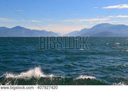 Lake Landscape, Blue Water, White Clouds, Mountains In Haze. Lake Garda In Italy