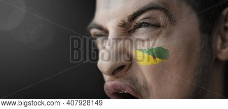 A Screaming Man With The Image Of The French Guiana National Flag On His Face
