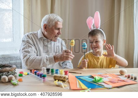 Happy Elderly Man Granfather Preparing For Easter With Grandson. Portrait Of Smiling Boy With Bunny