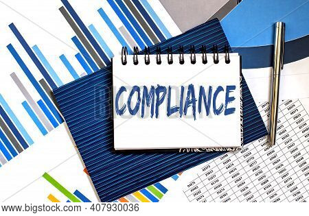 Notebook With Text Compliance On Office Table With Office Supplies On The Chart Background