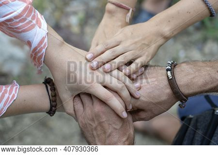 Arm Stacked Together One By One In Unity And Teamwork. Many Hands Getting Together In The Center Of