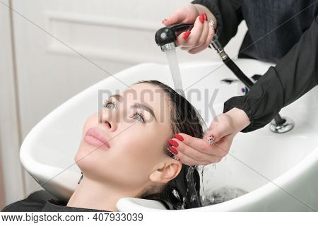 Professional Hairstylists Hands Wash Long Hair Of Brunette Woman With Shampoo In Professional Sink F