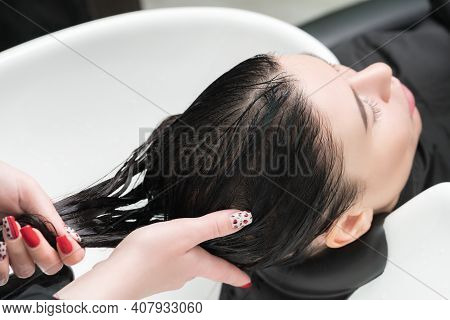 Hairdressers Hands Wash Long Hair Of Brunette Woman With Shampoo In Special Sink For Shampooing In H