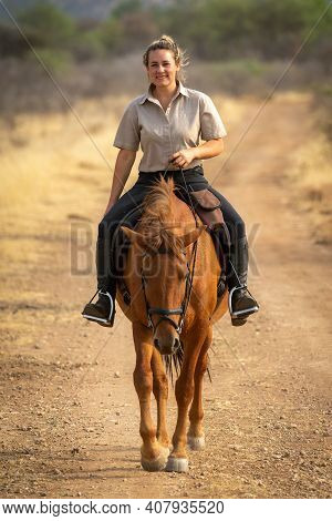 Smiling Blonde Rides Horse On Dirt Track