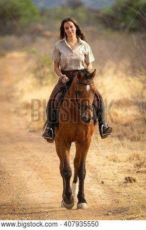 Smiling Brunette Rides Horse On Dirt Track
