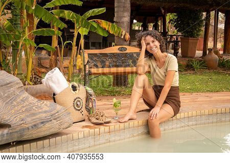 Smiling Brunette Sits By Pool Near Bench