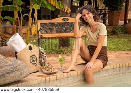Smiling Brunette Sits By Pool With Bag