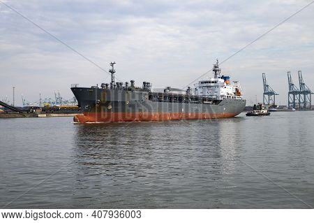 The Photo Shows A Tanker Ship Pulled By A Harbor Tugboat