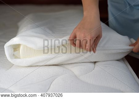 Women's Hands Put A Cover On The Orthopedic Pillow. Protecting The Foam Pillow From Moisture