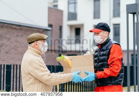 Young Male Volunteer In Mask Gives An Elderly Man Boxes With Food Near Her House. Son Man Helps A Si