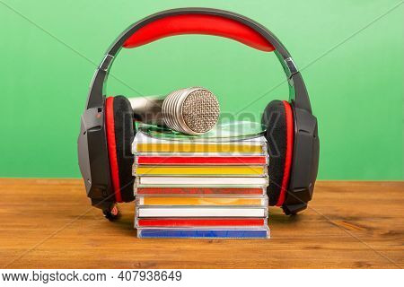 Headphones With Cds And An Audio Microphone On A Wooden Table, On A Green Background.
