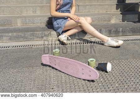 Teenager Girl Sitting On Stone Steps Near An Inverted Skateboard And A Cup Of Coffee. Skateboard And