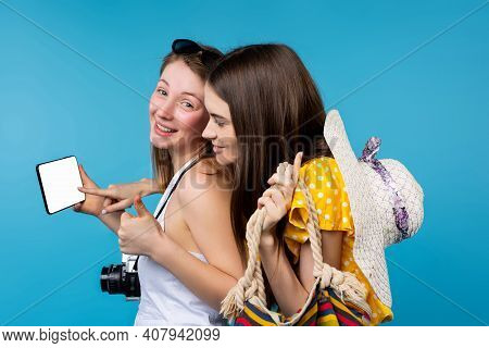 Happy Female Teen Tourists Showing A Blank Mock Up Mobile Phone Screen. Girls In Summer Clothes, Sea