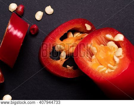 Red Chili Peppers Cut Into Pieces On A Black Background. Hot , Red Chili. Cook At Home. High Quality