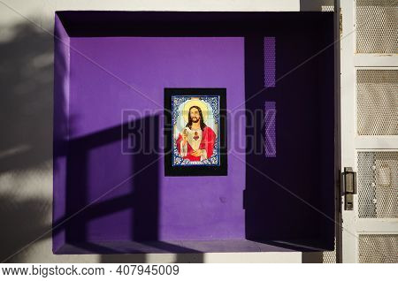Colorful Icon In Frame Of Jesus Christ On Purple Wall On The Street In Puerto Madryn Town. Mosaic Im