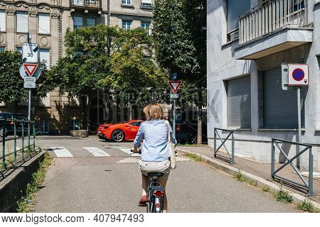 Strasbourg, France - - July 29, 2017: Rear View Of Single Woman Cycling On The French Street With Re