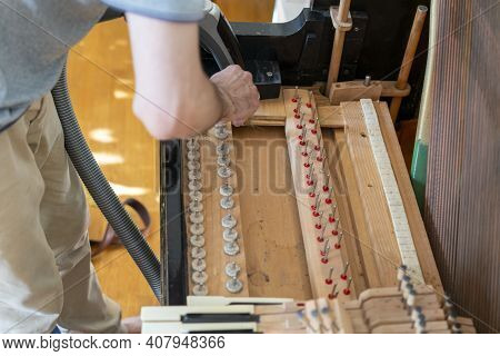 Setting Up An Old Piano. The Master Repairs An Old Piano. Deep Cleaning The Piano. Hands Of Professi