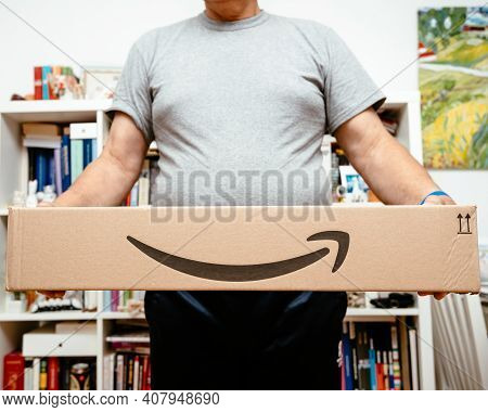 Paris, France - Oct 10, 2019: Lower Part Of Senior Man Smiling While Holding Two New Amazon Prime Pa