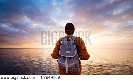 A Charming Calm Young Woman Stands By The Sea Expressing Delight.