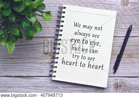 Motivational And Inspirational Quote On Notebook With Pen And Plant On Wooden Desk - We May Not Alwa