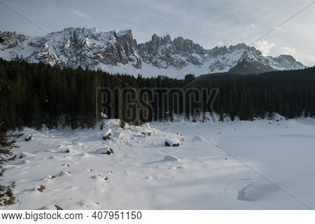 Karersee, Lago Di Carezza In Winter With Latemar Covered In Snow In The Background. Latemar Mountain
