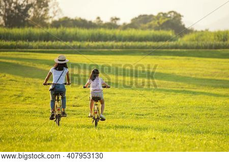 Family Happy.  Mother And Daughter Smiling Happy Outdoor With Bicycling At The Garden Meadow In Suns