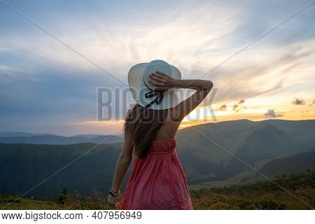 Young Happy Woman Traveler In Red Dress Standing On Grassy Hillside On A Windy Evening In Summer Mou
