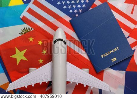 Avia Travel Theme. The Figure Of A Passenger Plane, Passport On The Background Of Many Flags Of Coun