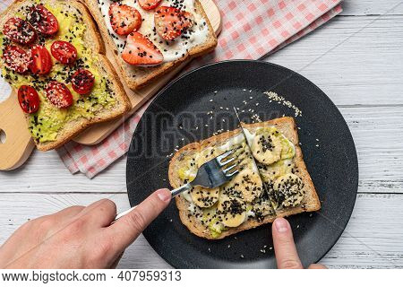 The Hand Was Using A Knife And Fork To Cut The Banana Toast. Concept Of Healthy Eating, Dieting, Veg