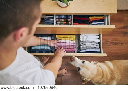 Organizing And Cleaning Home. Man Preparing Orderly Folded T-shirts In Drawer With His Curious Dog.