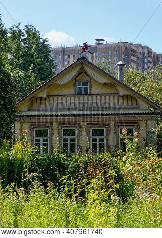 Beautiful Rural Wooden House On Background Of A High-rise Building, Russia