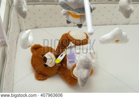 Brown Teddy Bear With Diaper On  Sitting In Baby Bed