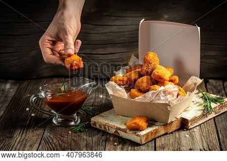 Hands Holdin Chicken Nuggets In Ketchup In Paper Box On A Wooden Background. American Food Concept.