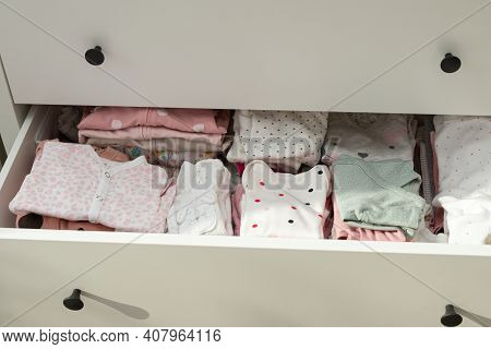 Cute Little Newborn Baby Clothes Arranged In A Drawer