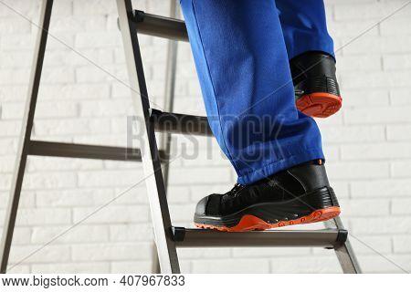 Professional Worker Climbing Up Ladder Indoors, Closeup